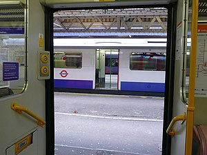 Spanish solution - Looking from one train through another, with doors open on both sides, to a third train.  At Barking in London, England eastbound Underground trains open their doors on both sides for cross-platform interchange with two main-line services, C2C and London Overground Barking - Gospel Oak, this photograph from inside one of the latter.