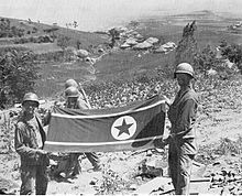 Soldiers hold a North Korean flag