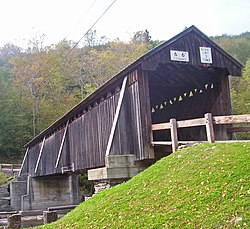 A dark brown covered bridge viewed from below and to the left of one of its portals with weight and height limitation signs