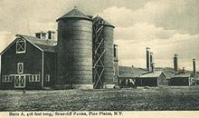 A large barn and silos