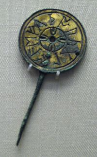 Pin with a large round head, on which eleven runic letters are carved in a circle around the edge