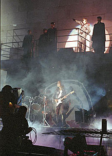 A concert stage in front of a wall with 2 levels. Five men stand on a balcony, including Roger Waters, who is saluting with his arm and is lit by a spotlight. On the lower level is a drum kit and a man playing guitar.