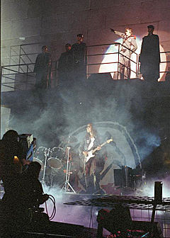 Konserttilava 2 tason seinän edessä.  Viisi miestä seisoo parvekkeella, mukaan lukien Roger Waters, joka tervehti kättään ja on valaistuna valonheittimellä.  Alemmalla tasolla on rumpusetti ja mies, joka soittaa kitaraa.
