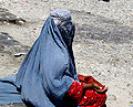 Burkha clad Afghan woman begs by the side of the road.jpg