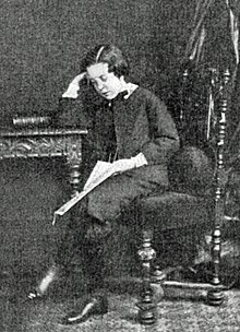young lad in Victorian dress, sitting at a desk