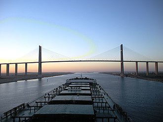 Suezmax - Post-deepening of the Suez Canal, larger ships pass through the canal – in this case, a capesize bulk carrier approaches the Egyptian-Japanese Friendship Bridge