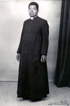 Cassock - First Native Roman Catholic parish priest from the Belgian Congo, wearing a Roman cassock. Note the 33 buttons, symbolizing the 33 years of the earthly life of Jesus Christ.