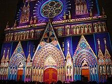 Vue en couleurs d'une façade de cathédrale, prise de nuit et illuminée de multiples couleurs.