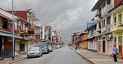 photographie d'une rue commerçante. Peu de circulation automobile (Il est près de 21.30), immeubles contigus avec un ou deux étages et boutiques au rez-de-chaussée