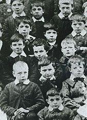 Photo en noir et blanc de plusieurs enfants en uniformes regardant l'objectif.