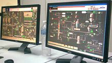 Two computer flat screens showing a plant process management application