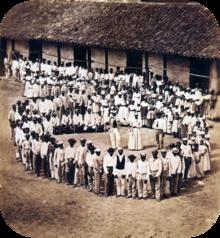 Fotografia que mostra um grupo de pessoas vestidas de branco, que se reuniram na frente de um edifício agrícola com telhado de telha e observar outro grande grupo que se formou um grande círculo em torno 5 homens abrangendo grandes tambores, uma mulher e 2 outros homens.