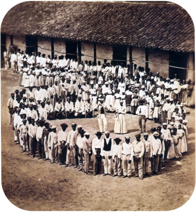 Photograph showing a group of people dressed in white, who have gathered in front of a tile-roofed farm building and observe another large group which has formed a large circle surrounding 5 men straddling large drums, a woman and 2 other men.
