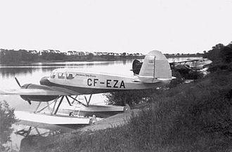Konrad Johannesson - Johannesson Flying Service Cessna Crane at Brandon Avenue Seaplane Base in Winnipeg, c. 1946, with a Noorduyn Norseman and a De Havilland Dragonfly tied up along the shore.