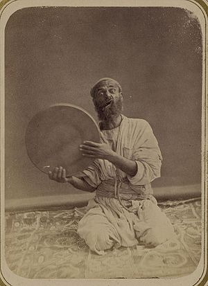 Tambourine - A traditional Central Asian musician from the 1860s or 1870s, holding up his dayereh.