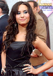 Smiling young woman with dark, wavy hair in a black dress