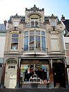 foto van Winkel-woonhuis op rechthoekige plattegrond in overgangsarchitectuur met zowel historiserende als aan de Weense Sezession ontleende motieven. Het winkel-woonhuis is opgenomen in een gesloten gevelrij