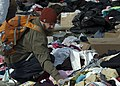 Displaced civilian searches for clothing. (Image 7 of 9) (8164586601).jpg