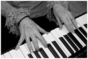 English: A woman plays an electronic keyboard....