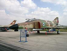 An aircraft with earth colored camouflage and Israel's roundel (blue Star of David on a white background).