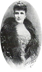 "Photo of Ronalds from the waist up, facing the camera. She is handsome and well-dressed, with a fur collar and an ""up"" hairdo."