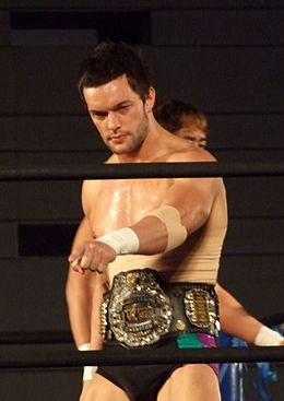 Prince Devitt with the IWGP Junior Heavyweight Championship belt in a wrestling ring