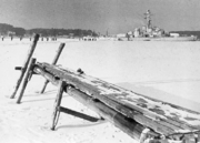 Frozen sea with a dock in front and a ship in behind.