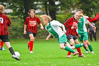 Foul (sports) - A player commits a foul by tripping an opponent during an association football match.