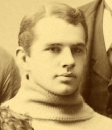 "A sepia picture of a young man in a sweater with a ""Y"""
