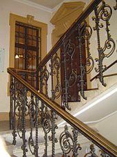 Scala decorata, pianerottolo con porta e finestra interna, scala che prosegue