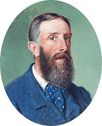 Oval shaped portrait of a bearded man, wearing a blue jacket and a blue, spotted cravat
