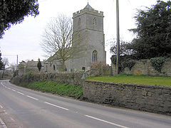 Stone building with square tower, separated from the road in the foreground by a stone wall.