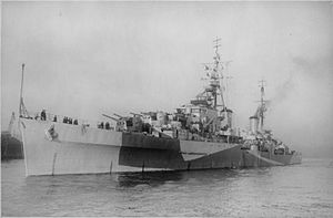 Black and white photo of a World War II-era warship. The ship is painted in camouflage and is armed with several gun turrets.
