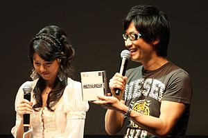 Metal Gear Solid - Hideo Kojima (with model Yumi Kikuchi) at the 2011 Tokyo Game Show holding a Metal Gear Solid jewel case
