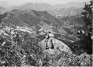 A man lies on a cliff overlooking a large hill complex
