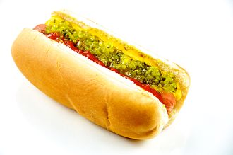 Hot dog - A cooked hot dog in a bun with mustard, relish, and ketchup
