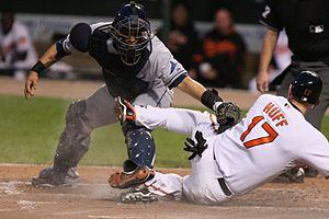 A baseball player tries to slide in to home plate while a catcher puts down a tag