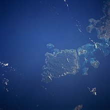 A satellite photo of Iriomote Island. Iriomote is in the center and is the largest island. There are other small islands surrounding it, and a portion of Ishigaki Island can be seen in the top-right of the iamge