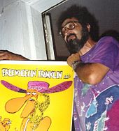 Photograph of a bearded man; he is wearing glasses and a watch, and holds in his hands a colorful poster depicting the comic character Freewheelin' Franklin