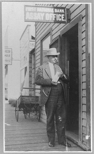 James Wickersham - Photo of James Wickersham standing in front of a First National Bank Assay Office, holding a gold (?) brick, cigar in mouth.