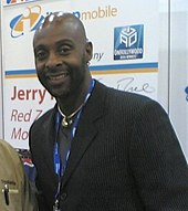 A bald Jerry Rice smiles. He is wearing a black suit.