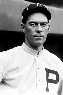 A man in a baseball uniform is shown from the chest up looking forward.