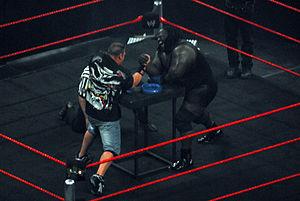 John Cena and Mark Henry in an arm wrestling m...
