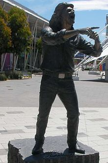 Statue of Farnham standing with a microphone in left hand at his opened mouth and pointing with right forefinger. Statue is on a block of stone with cursive lettering, John Farnham, in front of feet. Background includes a tiled area, wide footpath, trees and buildings.
