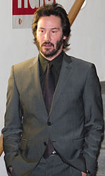 A candid portrait of Keanu Reeves wearing a gray suit.