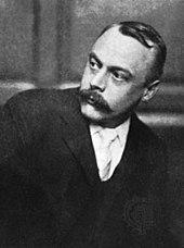 Photo en noir et blanc d'un homme moustachu d'une cinquantaine d'années aux cheveux courts et au visage tourné vers sa droite.