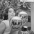 Kerstmis nadert jonge vrouw toont grote kerstballen, Bestanddeelnr 918-5562.jpg