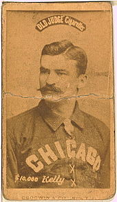 A baseball player is shown sitting, facing slightly left of the camera.