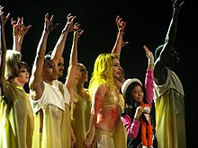 A grooup of dancers on stage wearing light yellow colored dress, and with their right hand stretched upwards in a claw shape. In their middle is a little girl wearing a pink dress and hat, and carrying a stuffed monkey.