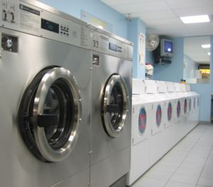 Image shows a line of washing machines in a laundromat.